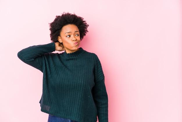 Donna afroamericana di mezza età contro uno sfondo rosa che tocca la parte posteriore della testa, pensando e facendo una scelta.