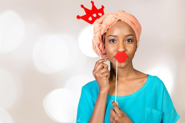 Donna afroamericana divertendosi con i puntelli della foto