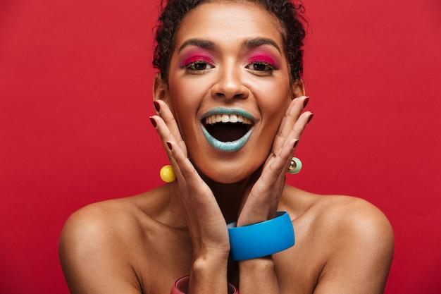 Donna afroamericana felice multicolore con trucco d'avanguardia che grida sulla macchina fotografica che si tiene per mano al fronte, sopra la parete rossa