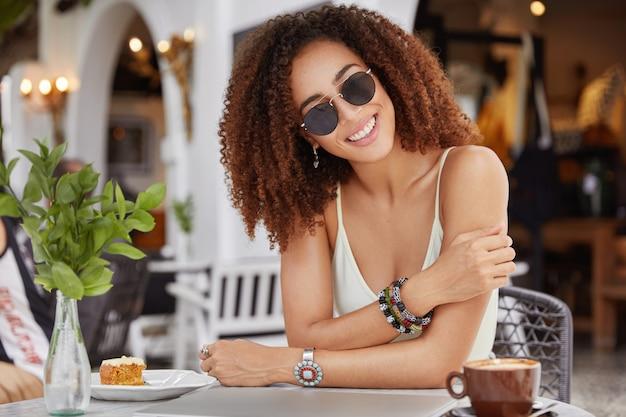 Donna afroamericana felice sorridente alla moda in occhiali da sole alla moda, beve caffè o latte, mangia la torta dolce, gode del tempo libero nella caffetteria