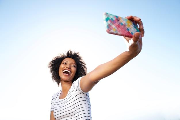 Donna afroamericana giovane di risata che prende selfie con lo smart phone all'aperto