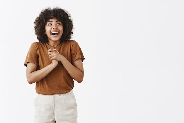 Donna afroamericana in forma eccitata e sognante con acconciatura afro che ride con gioia tenendo le palme vicino al cuore e guardando verso l'alto dalla felicità e dalla gioia sul muro grigio