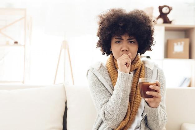 Donna afroamericana malata con seduta fredda sul divano.