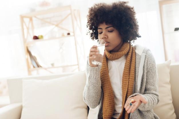 Donna afroamericana malata con seduta fredda sullo strato a casa