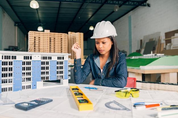 Donna afroamericana pensierosa nel casco di sicurezza vicino al modello di costruzione