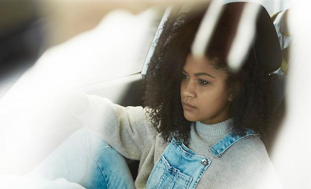 Donna afroamericana seduta in posa all'interno della sua auto