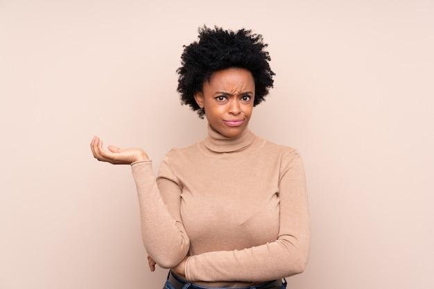 Donna afroamericana sopra la parete beige