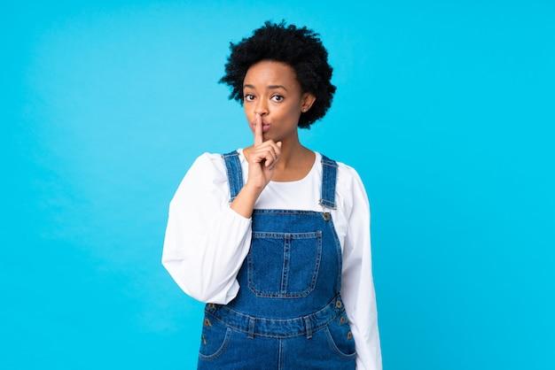 Donna afroamericana sopra la parete blu