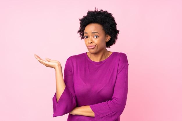 Donna afroamericana sopra la parete rosa
