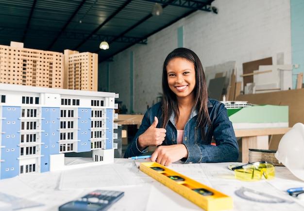 Donna afroamericana sorridente che mostra pollice vicino al modello di costruzione