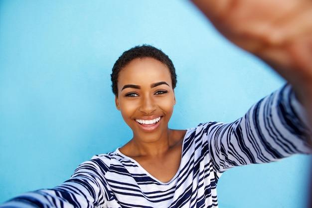 Donna afroamericana sorridente che prende selfie contro la parete blu