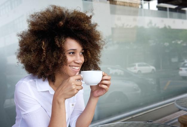 Donna afroamericana sorridente che si siede con la tazza di caffè
