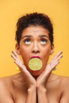Donna afroamericana sveglia verticale con trucco d'avanguardia che tiene metà di calce fresca in bocca isolata, sopra la parete gialla