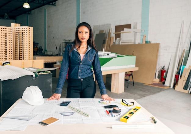 Donna afroamericana vicino tavolo con casco e attrezzature di sicurezza