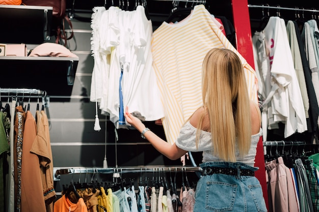 Donna agli acquisti che verifica i vestiti