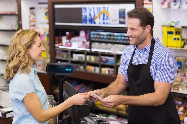 Donna al registratore di cassa pagando con carta di credito