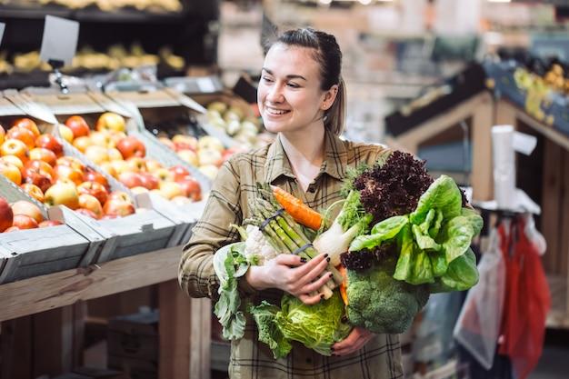 Donna al supermercato. bello acquisto della giovane donna in un supermercato e comprare le verdure organiche fresche