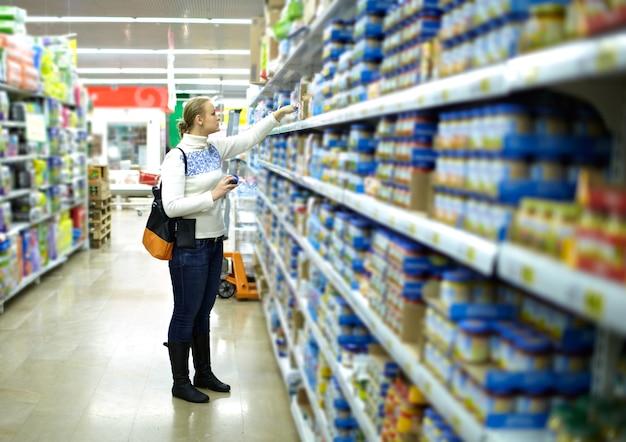 Donna al supermercato cibo per bambini.