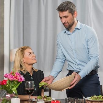 Donna al tavolo vicino uomo con ciotola di insalata