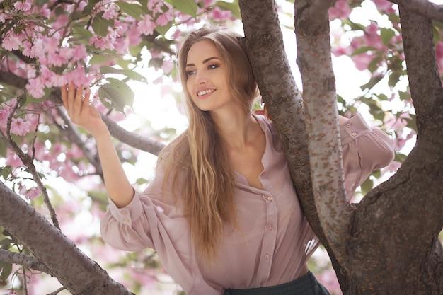 Donna all'albero sbocciante di sakura sulla natura