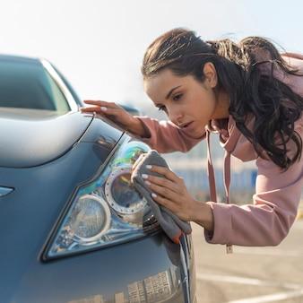 Donna all'aperto che pulisce l'automobile