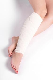 Donna alla caviglia su un muro bianco trascinato bendaggio elastico