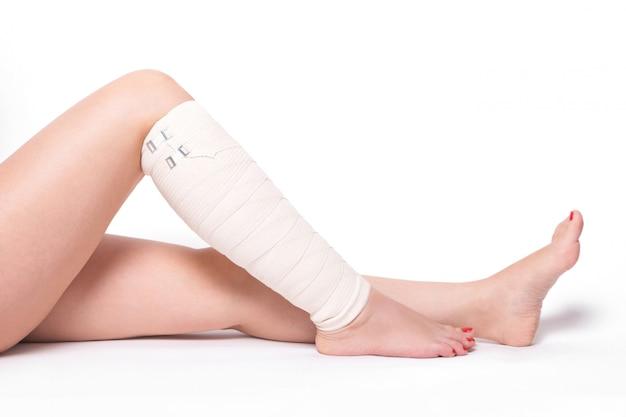 Donna alla caviglia trascinata bendaggio elastico