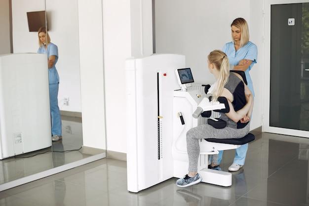 Donna alla fisioterapia facendo esercizi fisici con terapista qualificato