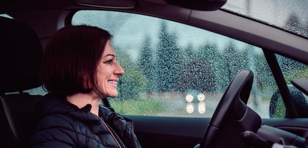 Donna alla guida di auto in autostrada sotto la pioggia