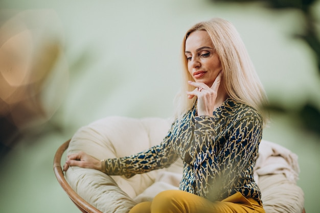 Donna alla moda adulta che si siede nella sedia