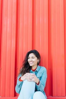 Donna alla moda che distoglie lo sguardo seduta su sfondo luminoso
