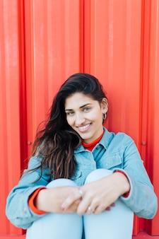 Donna alla moda che guarda l'obbiettivo mentre seduto davanti a sfondo rosso