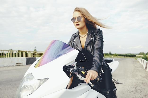 Donna alla moda che guida una bici su una strada