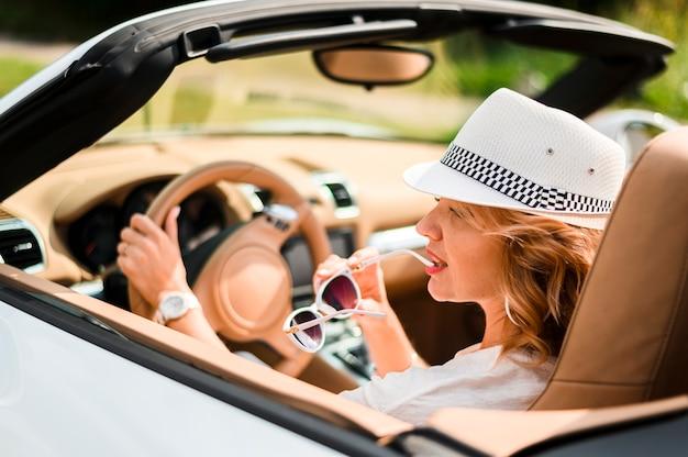 Donna alla moda che guida vista posteriore