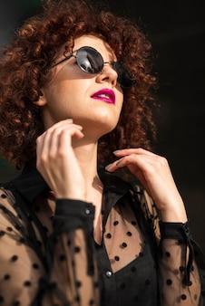 Donna alla moda che osserva a partire dalla macchina fotografica
