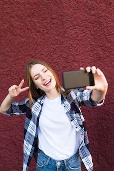 Donna alla moda che prende selfie con il gesto del segno di pace