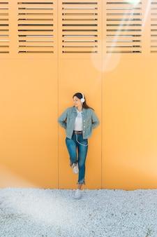 Donna alla moda che si appoggia sulla parete gialla che indossa l'auricolare