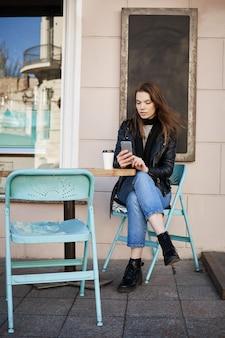 Donna alla moda che si siede nel patio del ristorante, bere caffè e prendere appuntamento al cosmetologo via internet, tenendo smartphone e digitando