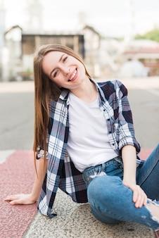Donna alla moda che si siede sulla strada che guarda l'obbiettivo