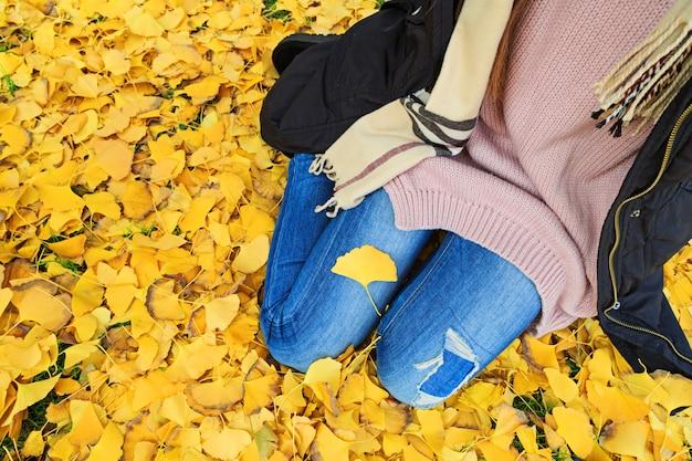 Donna alla moda che si siede sulle foglie gialle cadute del gingko