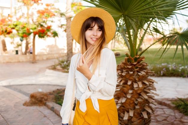 Donna alla moda che sta sulle palme e sugli alberi di fioritura. indossa un cappello di paglia.