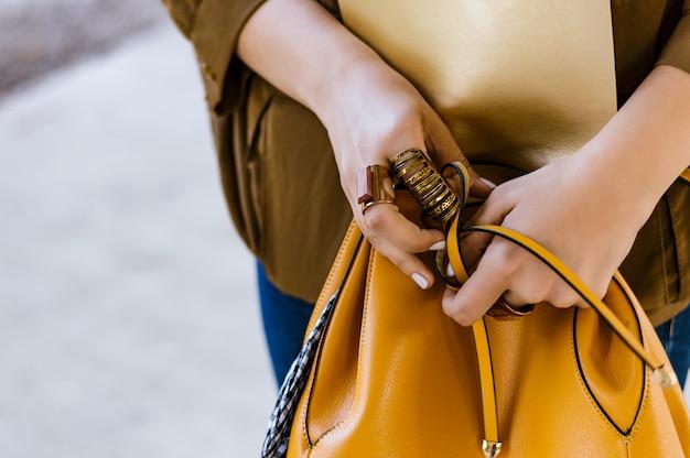 Donna alla moda che tiene una borsa in mani, fine in su