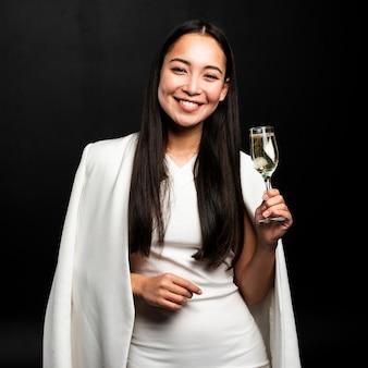 Donna alla moda che tiene vetro di champagne