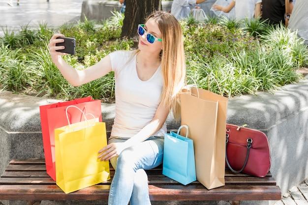 Donna alla moda con borse della spesa prendendo selfie