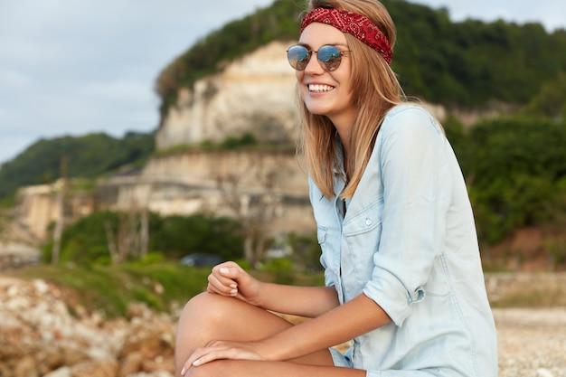 Donna alla moda con gli occhiali da sole che si siedono sulla spiaggia