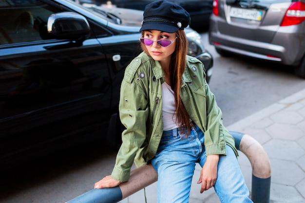 Donna alla moda con i capelli lunghi della brunetta che posano all'aperto nella grande città vicino alla strada