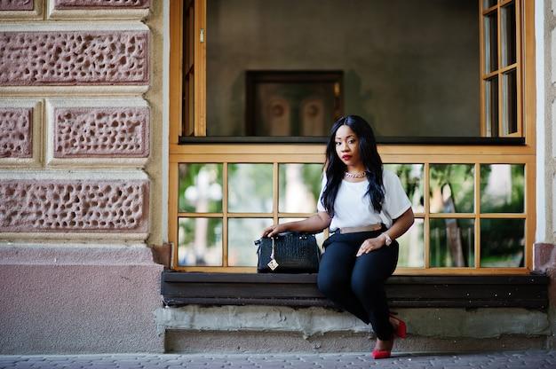 Donna alla moda di affari dell'afroamericano con la borsa sulle vie della città.