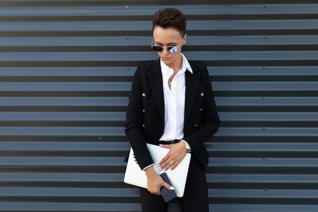 Donna alla moda di affari sullo sfondo di un edificio alla moda ufficio