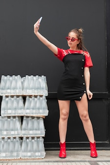 Donna alla moda di angolo basso che prende selfie