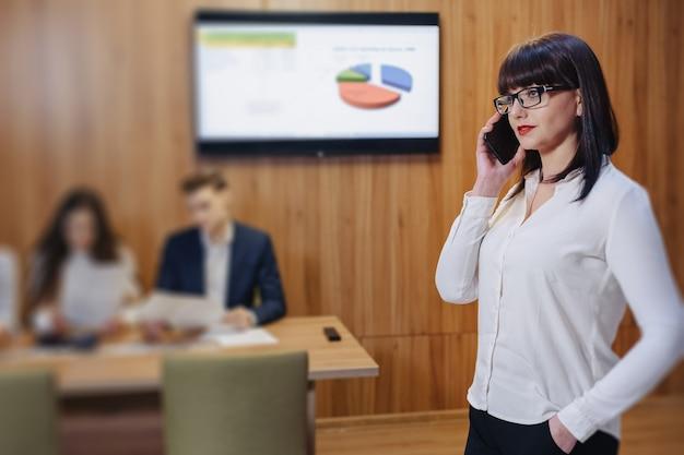 Donna alla moda di impiegato in vetri con il telefono in mano